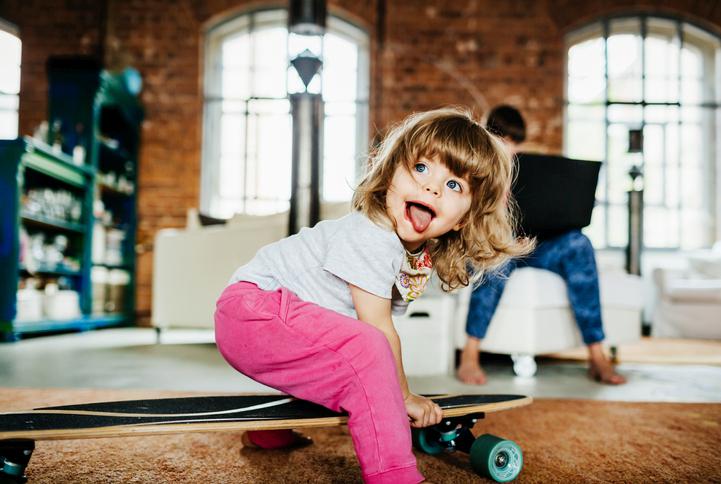 Bokeh Effekt: Mädchen spielt mit Skateborad in Innenraum