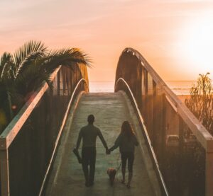 Paarfotografie / Pärchen Bilder Idee: Spaziergang zum Meer bei Sonnenuntergang