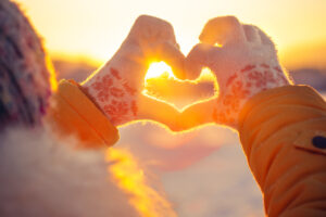Paarfoto Idee zum Valentinstag Herzhände vor Sonnenuntergang