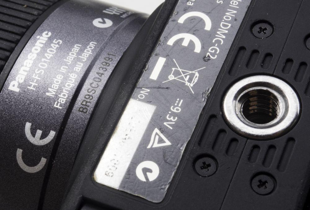 Die eingravierte Seriennummer des Objektivs ist gut erkennbar, doch die ins weiße Feld gedruckte Kamera-Seriennummer erscheint bereits unleserlich.