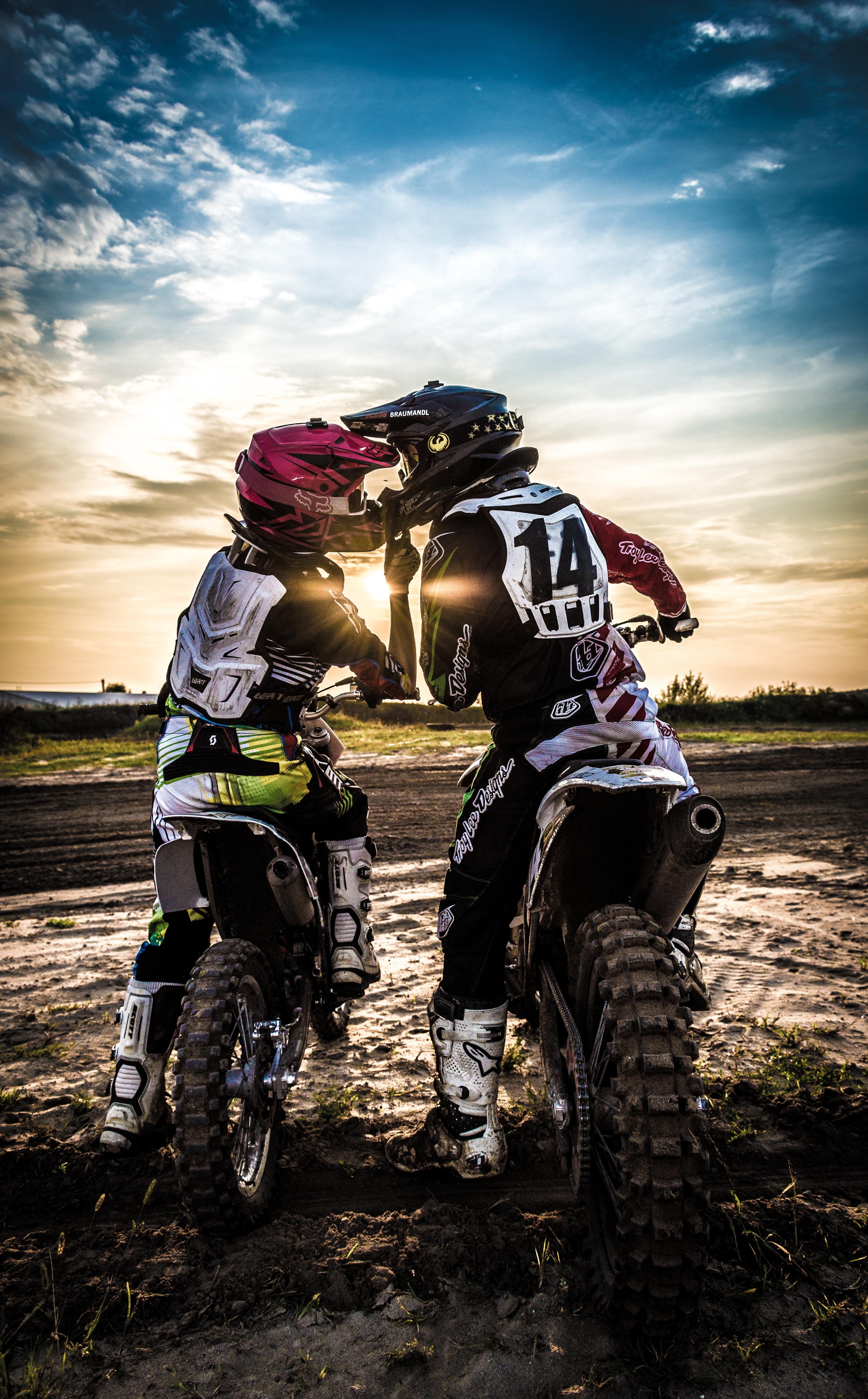 Paarfoto Mann und Frau auf Motocross-Maschinen küssen sich