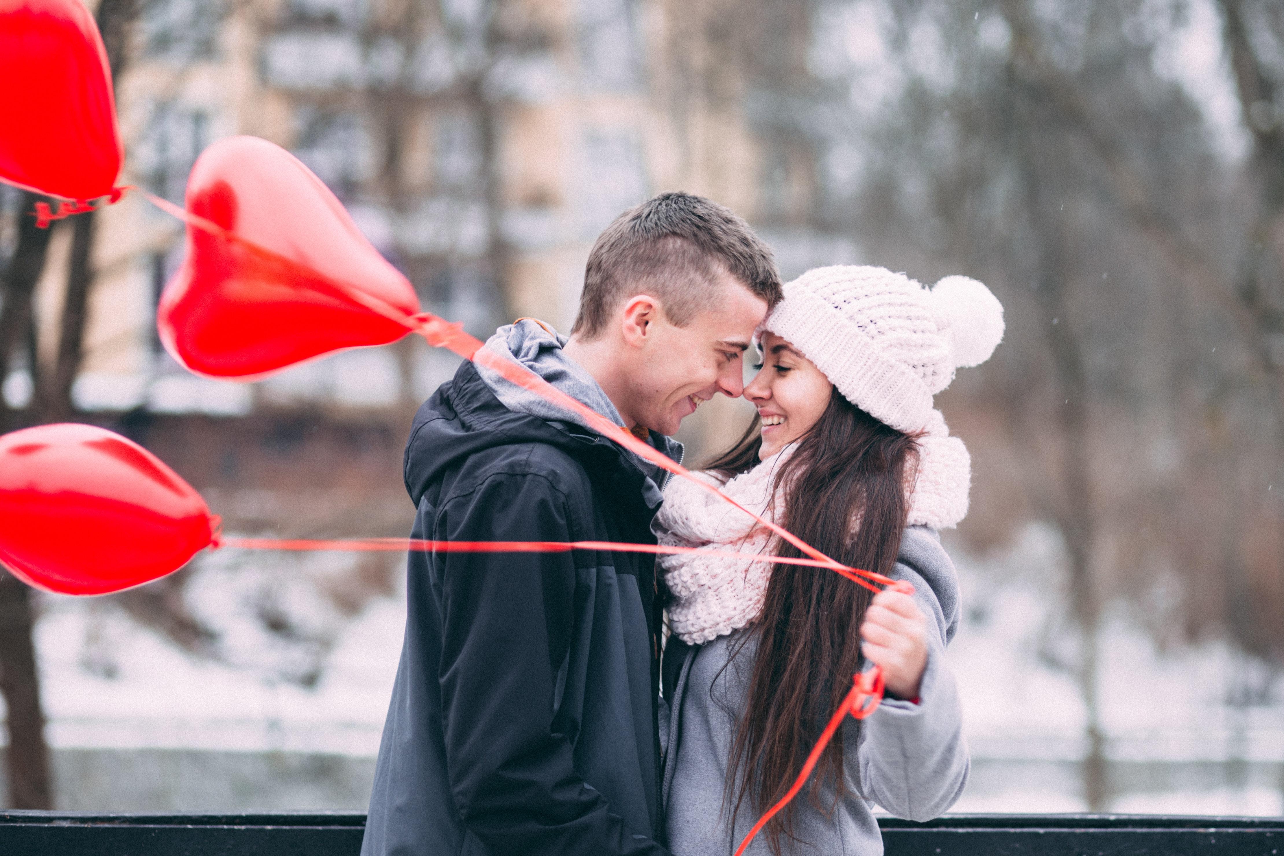 Paarfoto Mann und Frau mit roten Herz-Luftballons im Winter