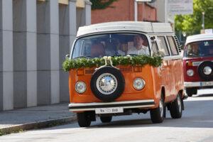 Hochzeitsfotografie Tipps: Orangefarbener VW-Bus als Hochzeitsauto mit Blumenschmuck