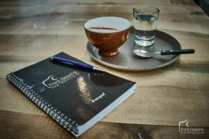 Auf einem Tisch steht ein Tablett mit Cappuchino und daneben liegt das Notizbuch des Hochzeitsfotografen