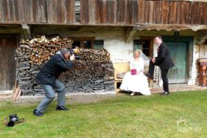 Hochzeitsfotografie Tipps: Der Fotograf und das Brautpaar beim Brautleute-Shooting vor einem Holzhaus