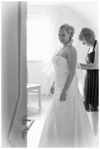Hochzeitsbilder Ideen: Die Braut beim Ankleiden in schwarz-weiß und im Gegenlicht fotografiert
