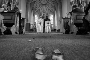 Hochzeitsbilder Ideen: Das Brautpaar vor dem Altar vom Boden aus fotografiert, auf dem Rosenblätter liegen
