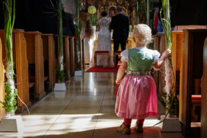 Hochzeitsbilder Ideen: Ein kleines Mädchen im Dirndl steht während der kirchlichen Trauung im Gang