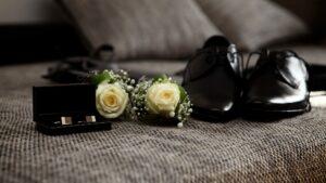 Hochzeitsbilder Ideen: Die Accessoires des Bräutigams, hier die Ringe, Blumen fürs Revers und die Schuhe