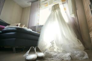 Hochzeitsbilder Idee: Das Brautkleid im Gegenlicht des Fensters vom Boden aus mit den Brautschuhen fotografiert.