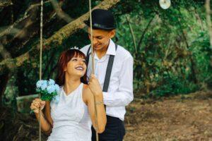 Hochzeitsfoto Ideen: Braut sitzt auf einer Schaukel unter einem Baum, der Bräutigam steht dahinter