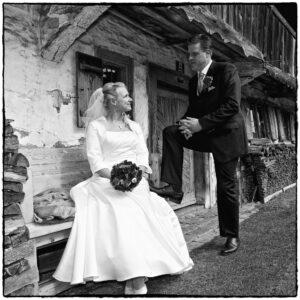 Hochzeitsfoto Ideen: Brautleute-Shooting vor einer Hütte in schwarz-weiß aufgenommen