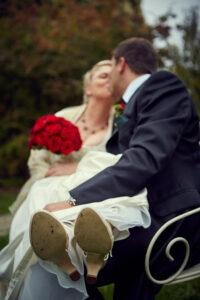 Brautleuteshooting - Hochzeitspaar sitzt sich küssend auf Bank