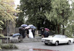Hochzeitsfoto Ideen im Regen: Hochzeitsgesellschaft mit Schirmen vor dem Hochzeitsauto