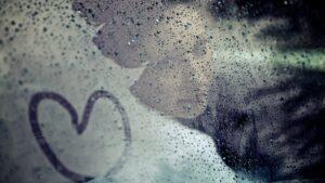 Hochzeitsfoto Idee im Regen: Die Braut hinter einer verregneten Autoscheibe, die von innen leicht beschlagen ist, und auf die mit dem Finger ein Herz gemalt wurde