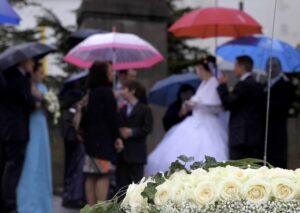 Hochzeitsfoto im Regen - Blumenschmuck scharf im Vordergrund und Hochzeitsgesellschaft mit Schirmen unscharf im Hintergrund
