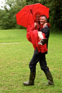 Hochzeitsfoto Ideen im Regen - Bräutigam mit Gummistiefeln trägt die Braut mit Schirm über eine Wiese