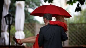 Hochzeitsfoto im Regen - Bräutigam trägt die Braut / Brautpaar mit Schirm von hinten fotografiert
