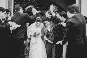 Brautpaar wird mit Reis beworfen - Hochzeitsfoto Idee für den Auszug aus der Kirche