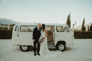 Hochzeitsfoto Ideen: Das Brautpaar vor dem Hochzeitsauto, hier ein weißer VW-Bus (Bulli)
