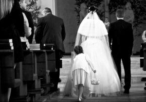 Brautpaar zieht in Kirche ein, Kind zupft Kleid zurecht