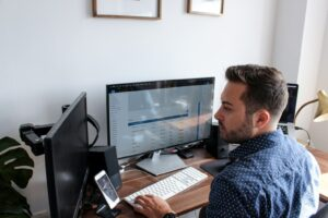 Hochzeitsbilder bearbeiten: Mann sitzt am PC und bearbeitet Fotos