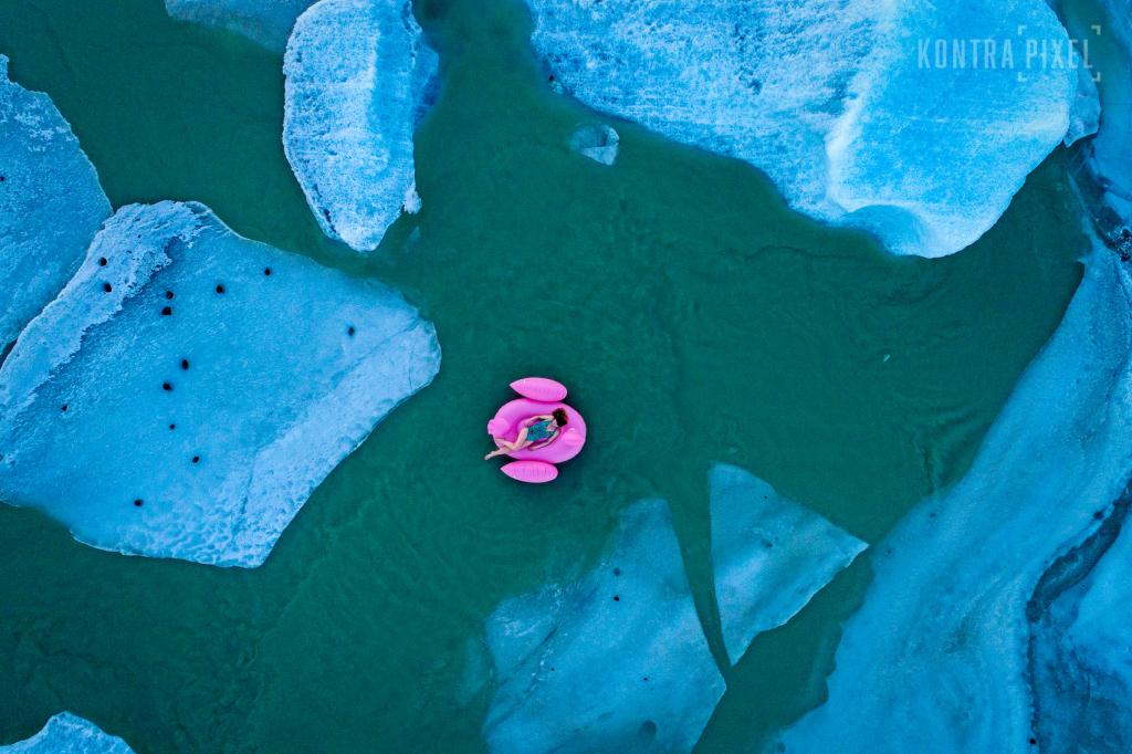 Drohnenaufnahme in Island: Eine Frau liegt auf einem pinkfarbenen Schwimmtier-Pelikan im Badeanzug zwischen Eisschollen im türkisfarbenen Wasser