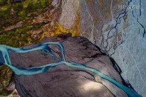 Drohnenfoto eines hellblauen Flussbettes durch eine graue Landschaft