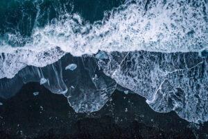 Drohnenfotografie: Wellen an einem schwarzen Strand mit Eisschollen