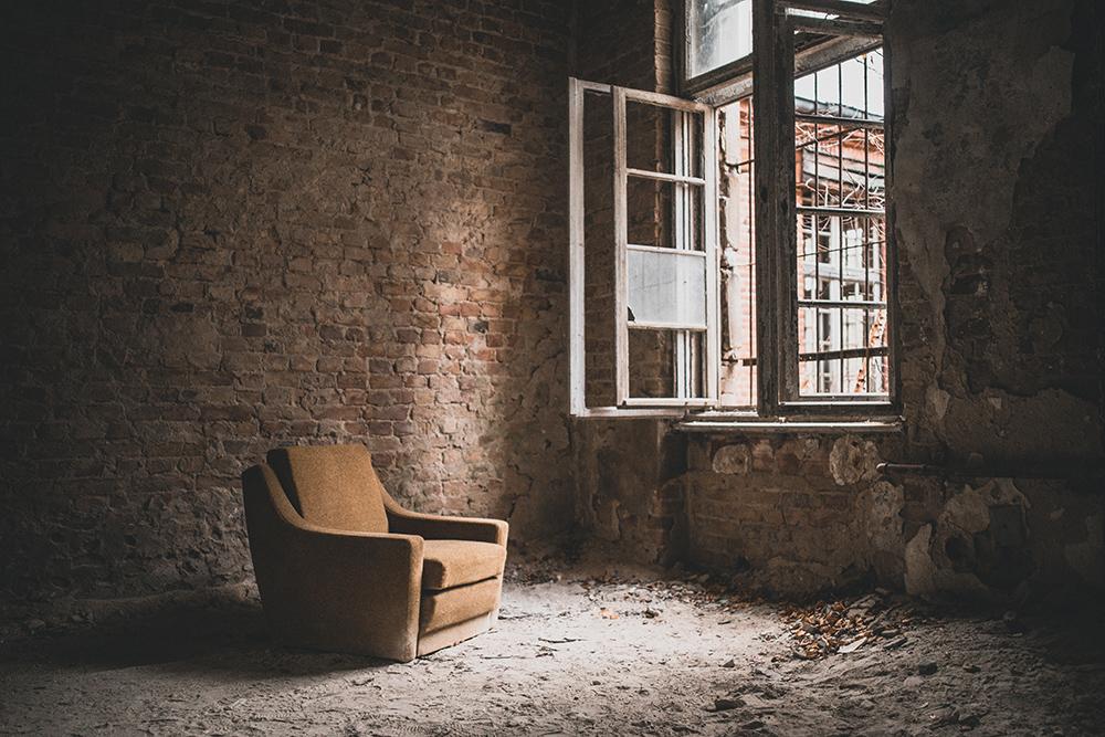 Urbexen: Sessel vor kaputtem Fenster